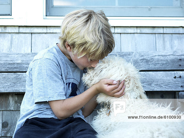 boy and his dog share a kiss