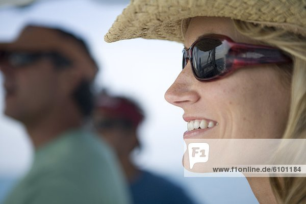 A close-up of a blonde woman as she looks out to the water wearing sunglasses and a straw hat.