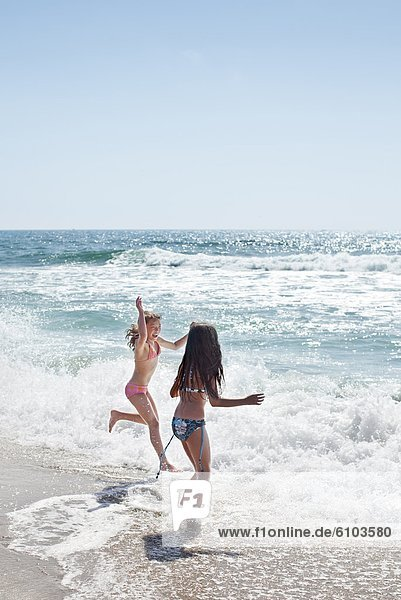 Two young girls playing in the waves at Torrance Beach in Los Angeles  California.