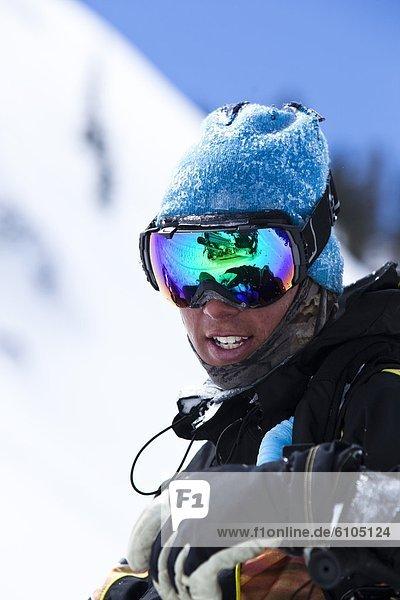 Portrait  Snowboardfahrer  lächeln  Schutzbrille  Spiegelung  unbewohnte  entlegene Gegend  Colorado  Schneemobil