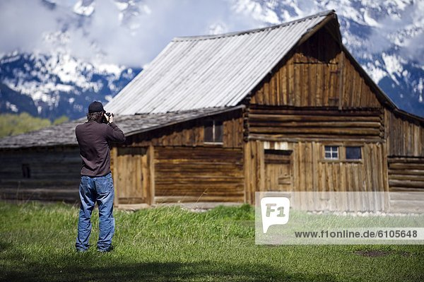 A photographer takes a picture of a historic barn on Mormon Row in Grand Teton National Park  Wyoming.