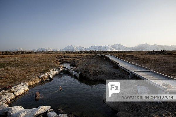 A man enjoys a hot spring near the mountains.