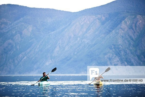 Two young adults kayaking on a lake in Idaho.