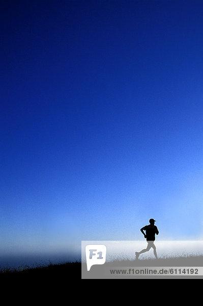 Mann  Silhouette  über  rennen  Ozean