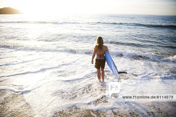 Wasser  Frau  tragen  Tischset  über  Surfboard  Wellenreiten  surfen  Mexiko  jung  Sonne  Brandung
