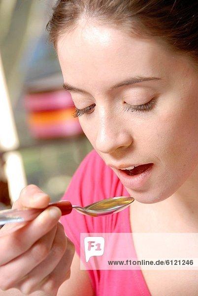 Frau  nehmen  Löffel  jung  Sirup