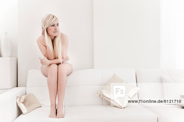Beautiful young blonde sitting on the couch and looking out the window