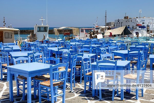 blue chairs a taverna at the fishing port of Naoussa  Paros  Greece