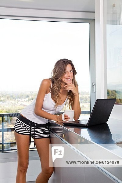 Pretty blonde woman with coffee and laptop in the morning at the kitchen