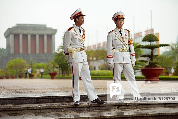 Officers in white uniforms standing guard on a side entrance to the Ho Chi Minh Mausoleum
