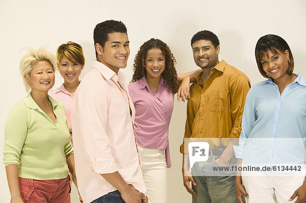 Group of young people standing together looking at camera smiling