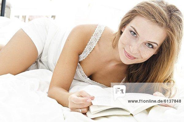 Lächelnde junge Frau liest ein Buch im Bett, Lächelnde junge Frau liest ein Buch im Bett