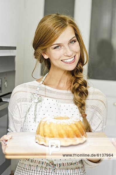 Lächelnde junge Frau mit einem Kuchen in der Küche