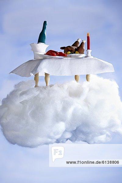 Gedeckter Tisch im Puppenformat steht auf Wolke aus Watte Gedeckter Tisch im Puppenformat steht auf Wolke aus Watte