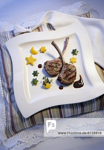 Teller mit Lammkoteletts und Zucchinis auf einem Kissen Teller mit Lammkoteletts und Zucchinis auf einem Kissen