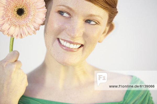 junge Frau hält eine Blume