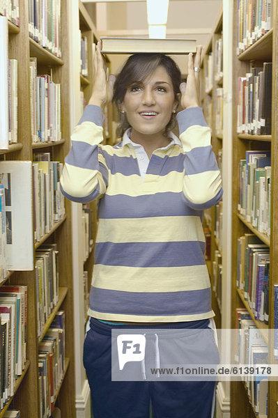 Jugendlicher  Buch  balancieren  Mädchen  Taschenbuch