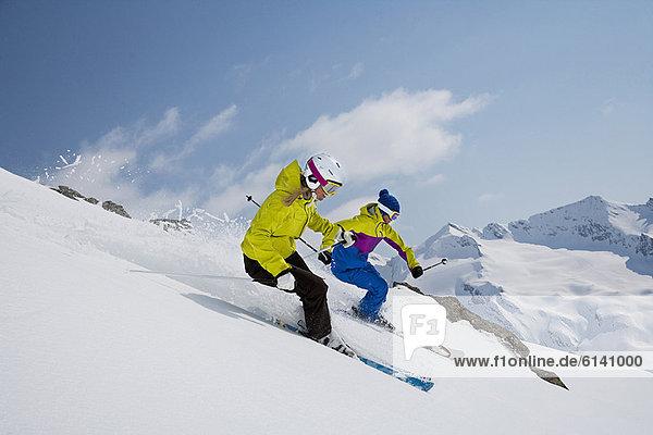 Skifahrer fahren auf verschneiter Piste