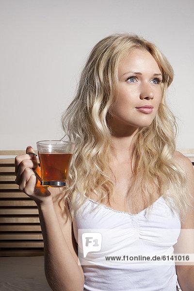 Frau trinkt Tee im Bett