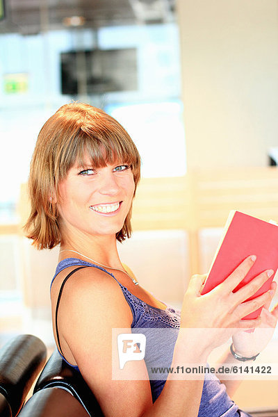 Smiling woman reading book in airport