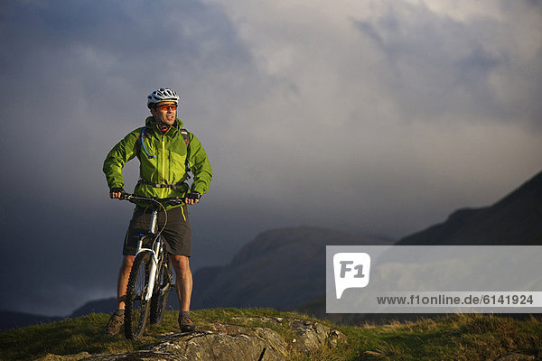Mountain biker on grassy hillside