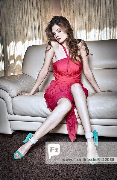 Frau im Cocktailkleid auf der Couch sitzend