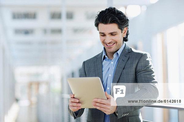 Mittlerer Erwachsener Geschäftsmann beim Betrachten des digitalen Tabletts  Portrait