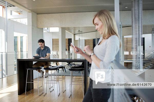 Geschäftsfrau mit Smartphone und Mann im Hintergrund