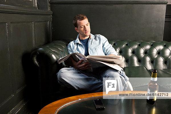 Mann liest Zeitung in der Kneipe