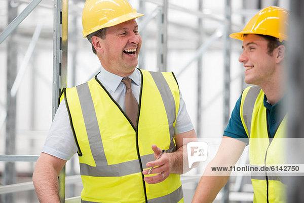 Zwei Männer  die im Lagerhaus lachen.