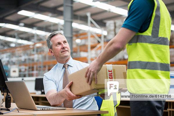 Mann  der einem anderen Mann einen Karton übergibt.