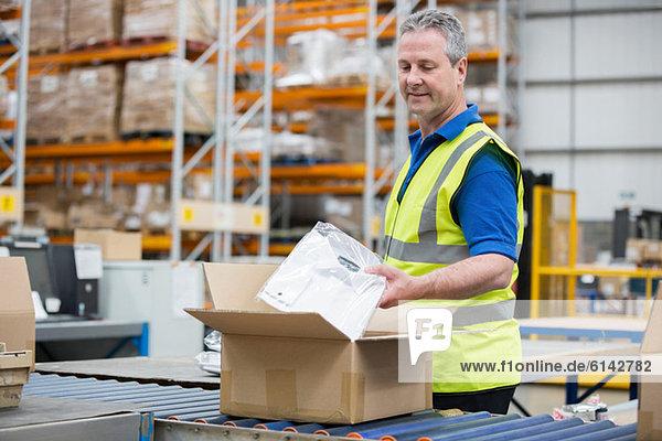 Mann verpackt Kleidung in einen Karton