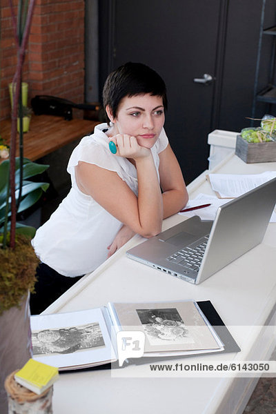 Businesswoman at desk with hand on chin