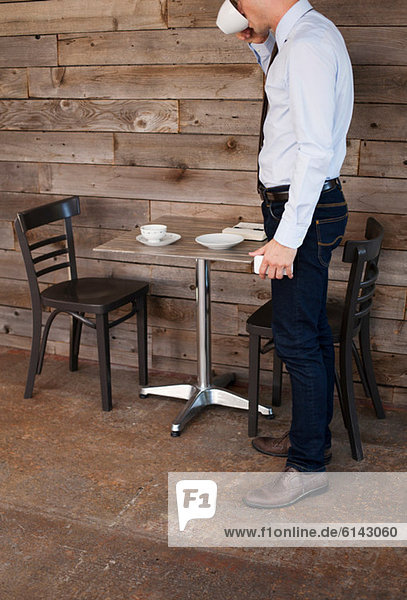 Businessman finishing drink in cafe