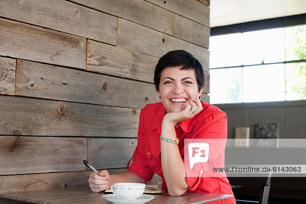 Woman wearing red shirt sitting in cafe  portrait