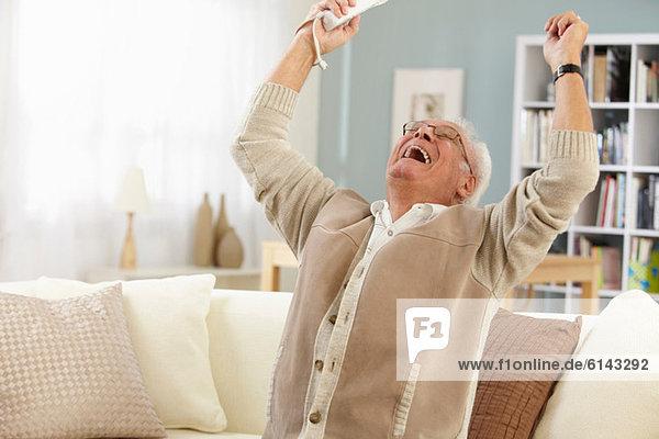 Älterer Mann mit Fernsteuerung jubelt