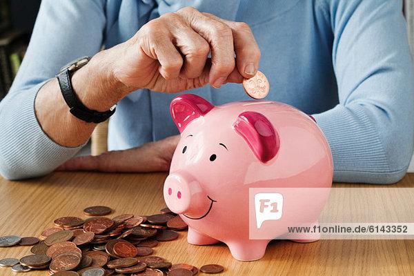 Seniorin beim Einwerfen von Münzen ins Sparschwein