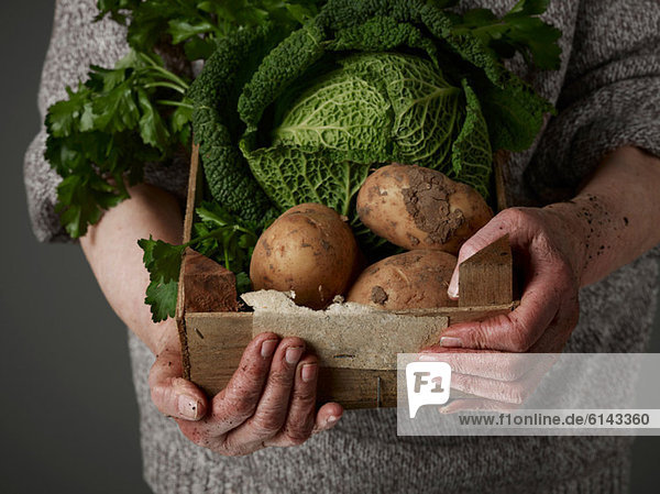 Frau hält Holzkiste mit Gemüse in der Hand