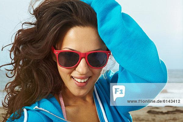 Junge Frau am Strand mit Hand im Haar und roter Sonnenbrille