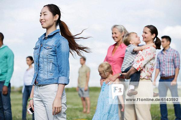 Junge Frau und Personengruppe im Freien