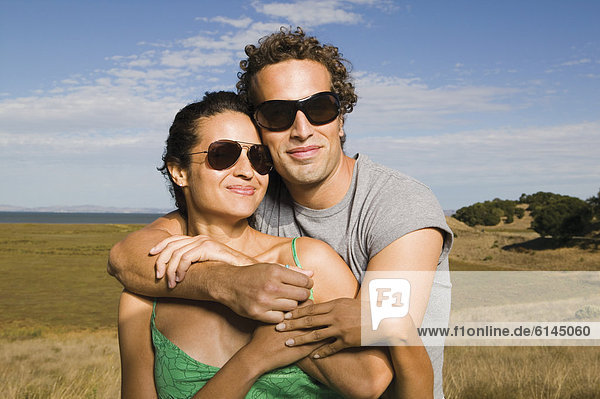 Portrait of couple wearing sunglasses and hugging