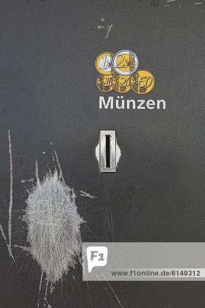 Geldeinwurf eines Parkscheinautomaten mit einer verkratzten Stelle vom Reiben der Geldmünzen  Deutschland  Europa