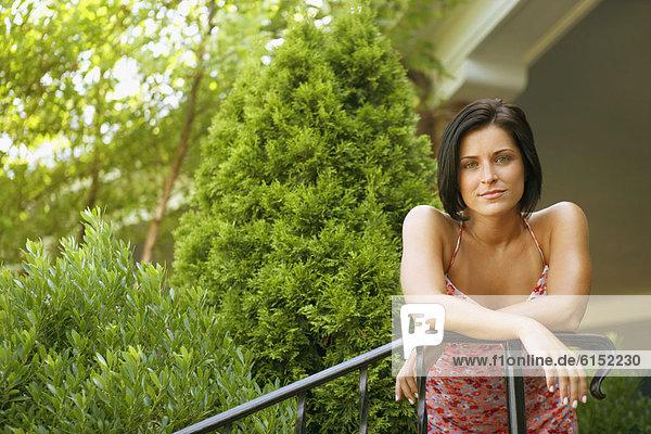 Junge Frau stützte sich auf Geländer