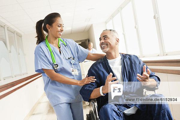 Nurse comforting patient in wheelchair in hospital