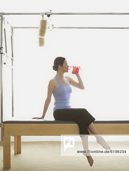 Woman drinking water on exercise equipment