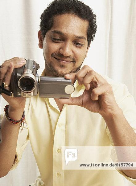 Indian man holding video camera