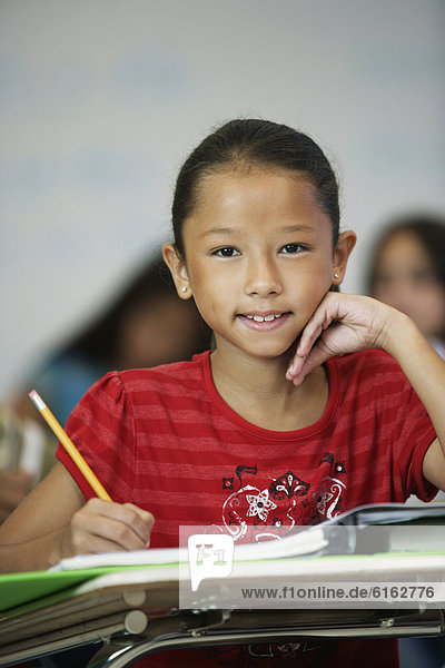 Asian girl at desk in classroom