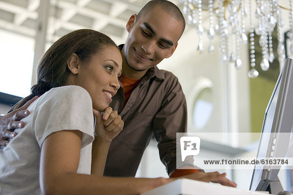 African American couple looking at computer
