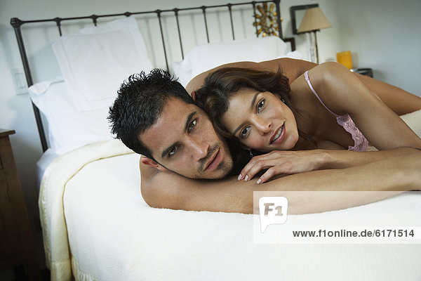 Hispanic couple hugging in bed
