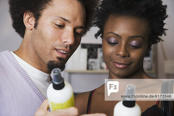 Multi-ethnic couple looking at hair product